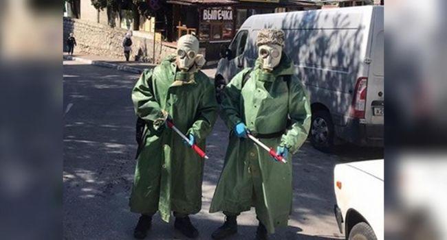 «Зато скрепно»: В аннексированном Крыму казаки, привлеченные к работам по дезинфекции, вышли на улицы в противогазах, надев сверху папахи